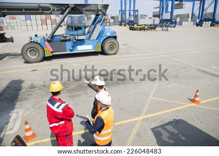High angle view of workers discussing in shipping yard - stock photo