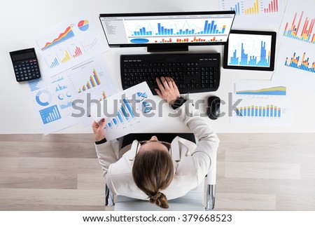 High Angle View Of Young Businesswoman Analyzing Graphs On Computer - stock photo