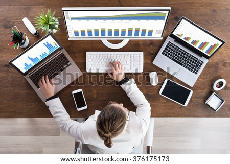 High Angle View Of Young Businesswoman Working With Graphs On Computer - stock photo