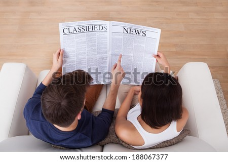 High angle view of young couple reading newspaper together on sofa at home - stock photo