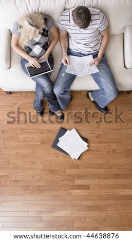High angle view of young couple sitting on a couch with a laptop and paperwork. Vertical shot. - stock photo