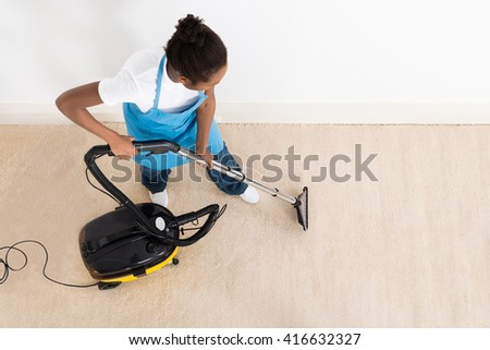 High Angle View Of Young Female Janitor Cleaning Floor With Vacuum Cleaner - stock photo