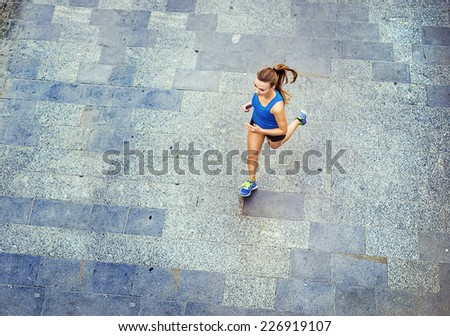 High angle view of young female runner jogging on tiled pavement old city on center. - stock photo