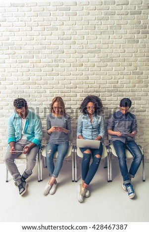 High angle view of young people of different nationalities using gadgets and smiling while waiting for interview - stock photo