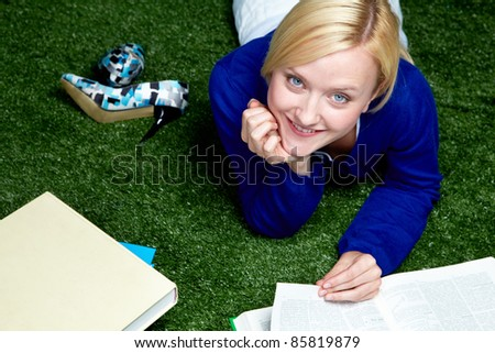 High angle view of young student lying on grass with textbooks - stock photo
