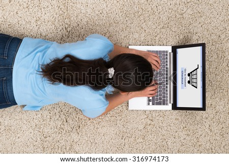 High Angle View Of Young Woman Doing Online Shopping On Laptop - stock photo