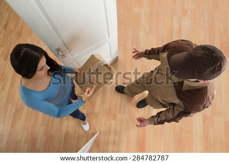 High Angle View Of Young Woman Receiving Damaged Package From Delivery Man - stock photo