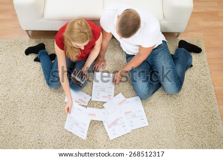High Angle View Young Couple Calculating Bills With Calculator At Home - stock photo