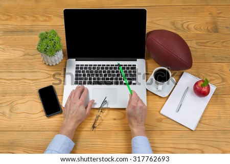 High angled view of male hand holding pencil, point at screen, while typing on computer keyboard. Game plan concept with football in background.  - stock photo