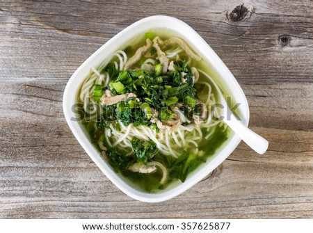 High angled view of noodle and vegetable soup with spoon in bowl on rustic wood.  - stock photo