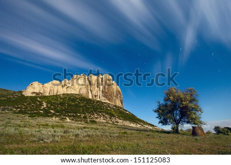 High cliff in a moon light with a beautiful moving clouds and lonely tree - stock photo