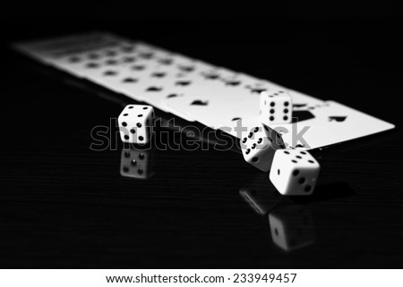 High contrast black and white image of gaming dice and a row of playing cards. - stock photo