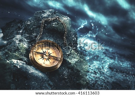 high contrast image of a compass on rocks - stock photo