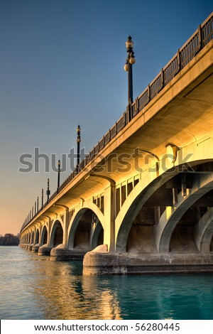 High dynamic range image of the MacArthur Bridge (once known as the Belle Isle Bridge) at sunset over the Detroit River in Detroit, Michigan. - stock photo