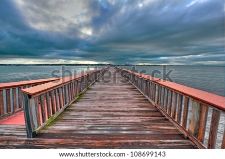 High Dynamic Range photo of a fishing pier on the Chesapeake Bay in Maryland near sunset. Factory and bridge in background - stock photo
