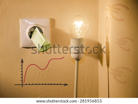 High electric bill metaphor, euro bill in power socket, next to light bulb graphic chart showing increasing price and euro shadows on the wall - stock photo