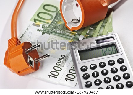 High electricity costs symbolized by connector, calculator and money. - stock photo