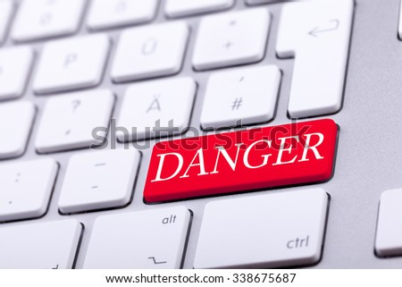 High end aluminium keyboard with DANGER word in red on it. Danger and alert - stock photo