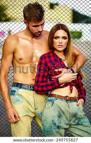 High fashion look.beautiful couple sexy stylish blond young woman model with bright makeup with perfect sunbathed skin and handsome muscled man in vogue style in jeans outdoors - stock photo