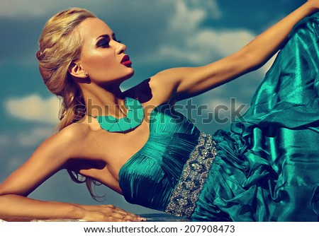 High fashion look. beautiful sexy stylish blond young woman model with bright makeup  red lips with perfect sunbathed skin with jewelery outdoors in vogue style in evening long blue dress behind sky - stock photo