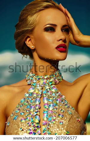 High fashion look.glamor beautiful sexy stylish blond young woman model with bright makeup and red lips with perfect sunbathed skin  outdoors in vogue style in evening dress behind blue sky - stock photo