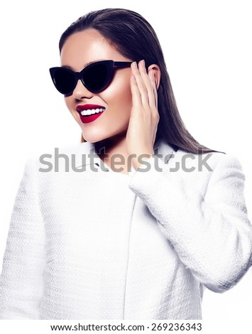 High fashion look.glamor closeup portrait of beautiful sexy smiling stylish brunette young woman model with bright makeup with red lips in white coat jacket in sunglasses - stock photo