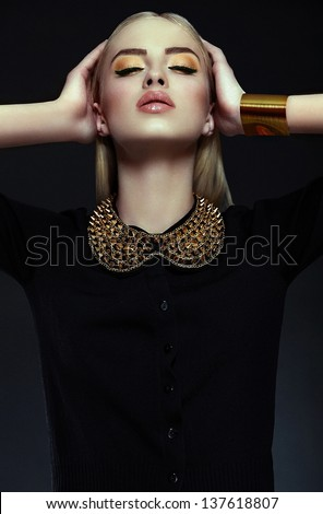High fashion look.glamor closeup portrait of beautiful sexy stylish blond  young woman model with bright yellow makeup  with perfect clean skin with gold jewelery in black cloth - stock photo