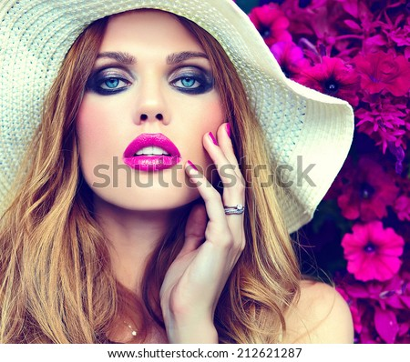 High fashion look.glamor closeup portrait of beautiful sexy stylish blond young woman model with bright makeup and pink lips with perfect clean skin in hat near summer flowers - stock photo