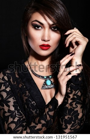 High fashion look.glamor closeup portrait of beautiful sexy stylish brunette Caucasian young woman model with bright makeup, with red lips,  with perfect clean skin with jewelery in black cloth - stock photo