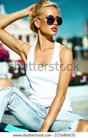 High fashion look.glamor stylish beautiful young blond  model girl teenager in summer bright casual hipster clothes with skateboard behind blue sky in the street - stock photo
