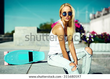 High fashion look.glamor stylish sexy beautiful young blond  model girl in summer bright casual hipster clothes with skateboard behind blue sky in the street - stock photo