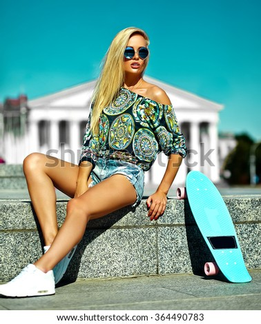 High fashion look.glamor stylish sexy beautiful young cute blond model girl in summer bright casual hipster clothes with skateboard sitting behind blue sky  - stock photo