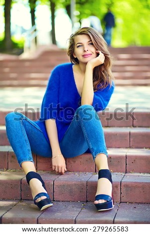 High fashion look.glamor stylish sexy smiling beautiful sensual young woman model in summer bright hipster cloth in blue jeans sitting  in the street - stock photo