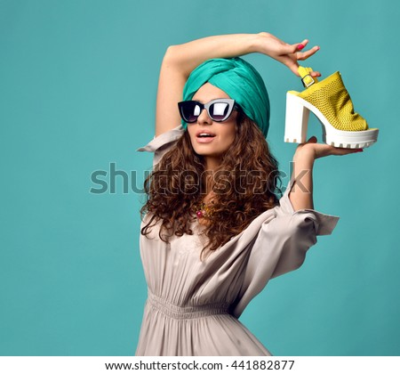 High fashion look glamour beautiful curly hair American woman in modern cat eyes sunglasses with white yellow shoe and nails manicure on blue mint background - stock photo