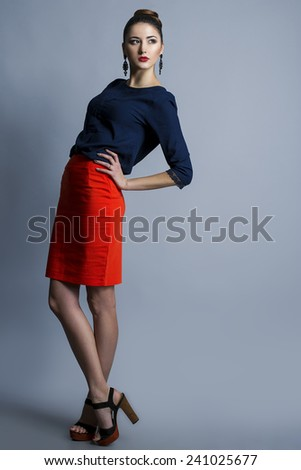 High fashion look. Portrait of a fashionable model with sexy red lips, beautiful red skirt and blue shirt. Studio shot - stock photo