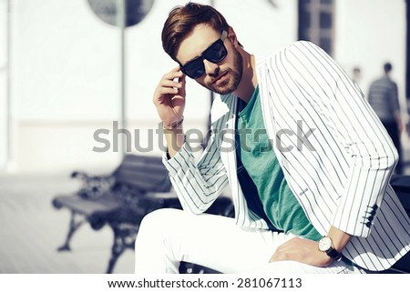 High fashion look.Young stylish confident happy handsome businessman model  in suit  lifestyle in the street in sunglasses - stock photo