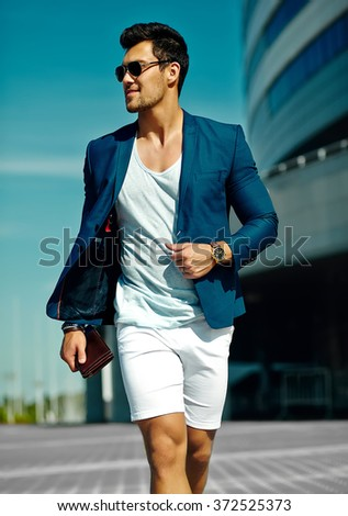 High fashion look.Young stylish confident happy handsome  businessman model man in blue suit cloth lifestyle in the street in sunglasses behind sky - stock photo
