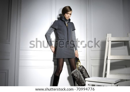 High fashion model holding bag posing wooden ladder in the studio - stock photo