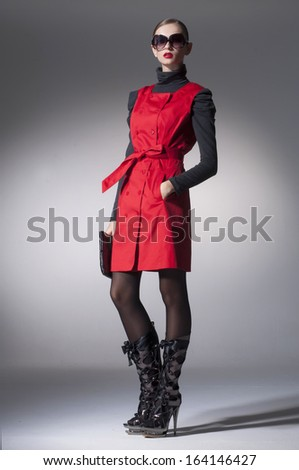 High fashion model in fashion red dress wearing sunglasses posing in the studio  - stock photo