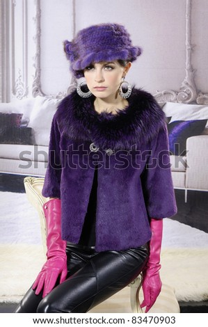 High fashion model in fur coat clothes posing in the studio - stock photo