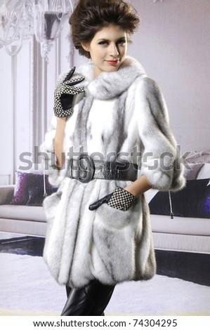 High fashion model in fur coat posing - stock photo