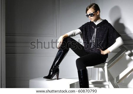 High fashion model in modern dress sitting in the studio - stock photo