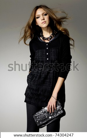 High fashion model with bag posing - stock photo