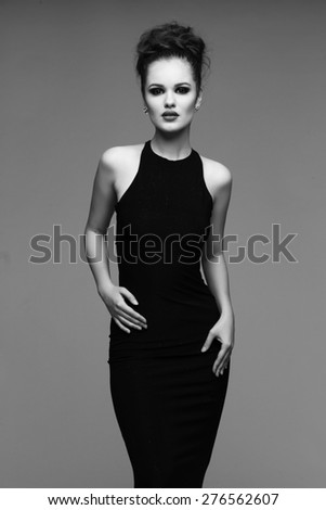 high fashion portrait of elegant woman in long black dress. Black and white studio shot - stock photo