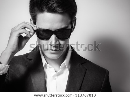 High fashion portrait of male model wearing sunglasses and a suit.  - stock photo
