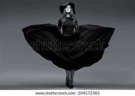 High fashion shot of elegant woman in a hat and long fluttering dress. Black and white image - stock photo