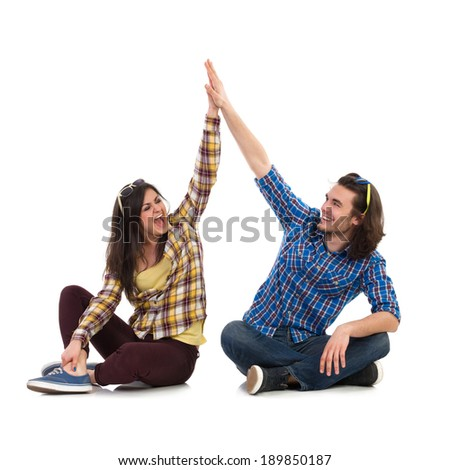 High five. Happy students sitting on the floor with legs crossed and giving high-five to each other. Full length studio shot isolated on white. - stock photo
