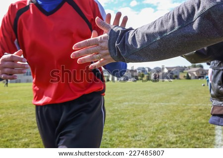 High Five line after a child's soccer game. Some motion blur, focus on arm - stock photo