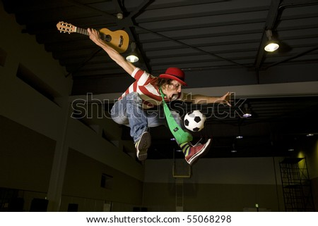 high flying crazy soccer fan with soccer ball - stock photo