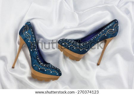 High-heeled shoes  lying on white  fabric, can use as background - stock photo